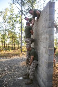 Marines with Weapons Company, 1st Battalion, 5th Marine Regiment, Marine Rotational Force - Darwin, work together to scale a wall at an obstacle course during a week-long squad competition aboard Robertson Barracks, June 2, 2014. Each squad will complete a variety of infantry obstacles and events that are either timed or scored against other competing squads. The rotational deployment of U.S. Marines affords an excellent combined training opportunity with the Australian Defence Force, and improves interoperability between both forces.